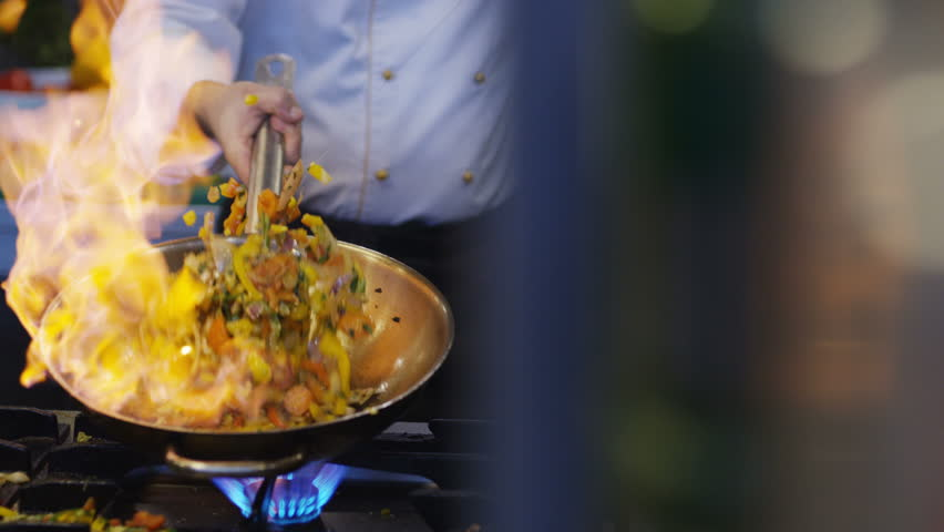 Cooking in wok pan with hard fire burning in slow motion | Shutterstock HD Video #1011806849