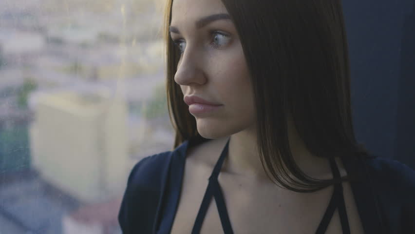 Sensual girl is standing next to the window | Shutterstock HD Video #1011807290