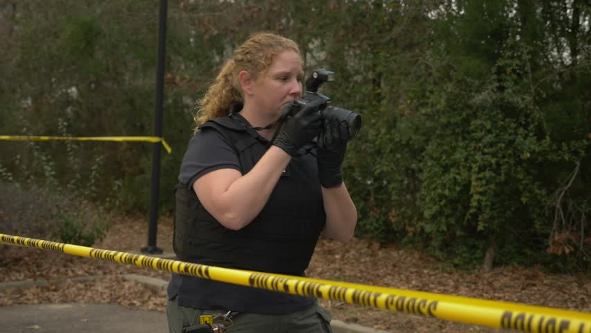 A crime scene investigator walks around and takes pictures of a crime scene with a camera.