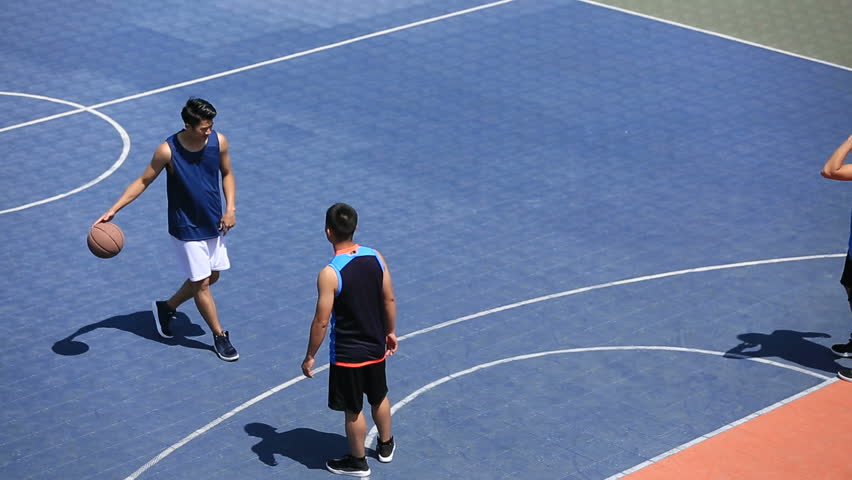 Young asian adults playing basketball on outdoor court, high angle view.