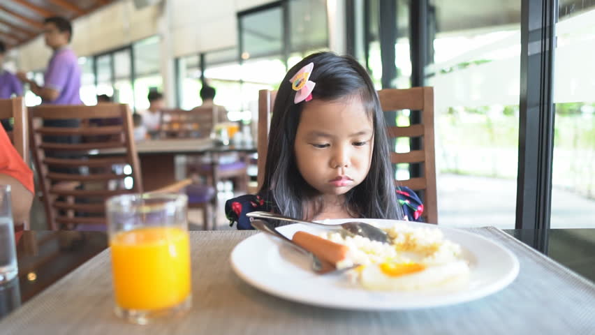 Asian children cute or kid girl student anorexia or sad with vacant on food table with fried rice, fried egg, sausage and orange juice for breakfast in restaurant before going to school for study