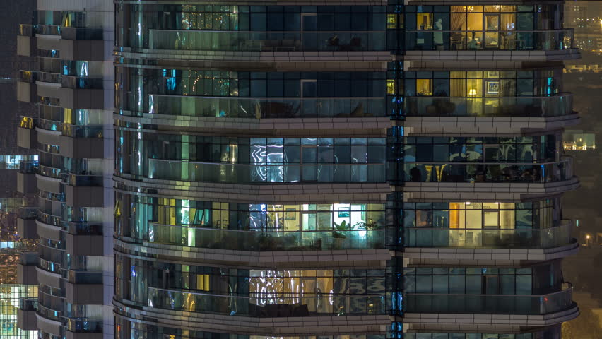 Windows of the multi-storey building of glass and steel lighting inside and moving people within timelapse. Aerial view of modern residential and office skyscrapers in Dubai marina. Pan down | Shutterstock HD Video #1011839693