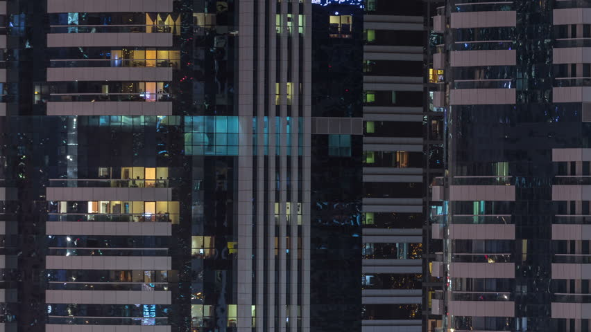 Windows of the multi-storey building of glass and steel lighting inside and moving people within timelapse. Aerial view of modern residential skyscrapers in Dubai. Zoom out | Shutterstock HD Video #1011840332