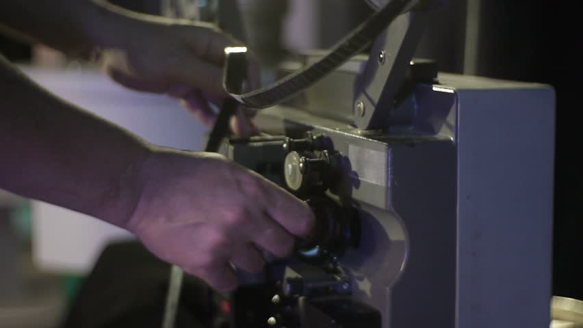 The mechanic charges the film in an old film projector. Close-up of a reel with a film #1011844004