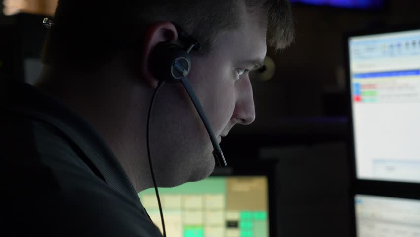 A 911 dispatcher works at his computer station at a control center to help respond to emergency calls.