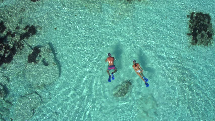 Couple Snorkeling In Shallow Turquoise Water