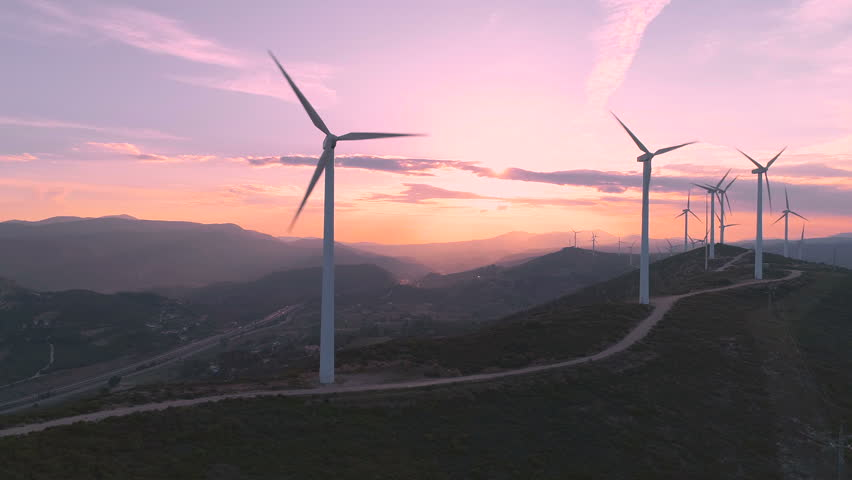 Wind turbine farm on beautiful purple evening mountain landscape. Renewable energy production for green ecological world. Aerial view of wind mills farm park on evening mountain. Lateral flight