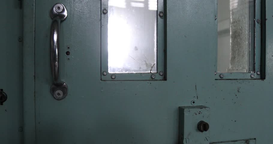 Door closing on solitary confinement cell in old prison.