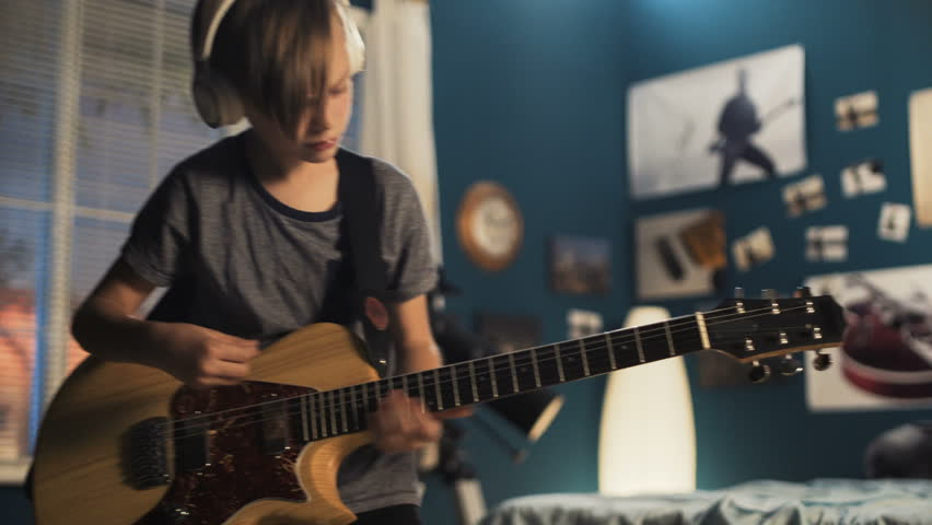 Expressive boy learning guitar play while standing in bedroom and playing with passion