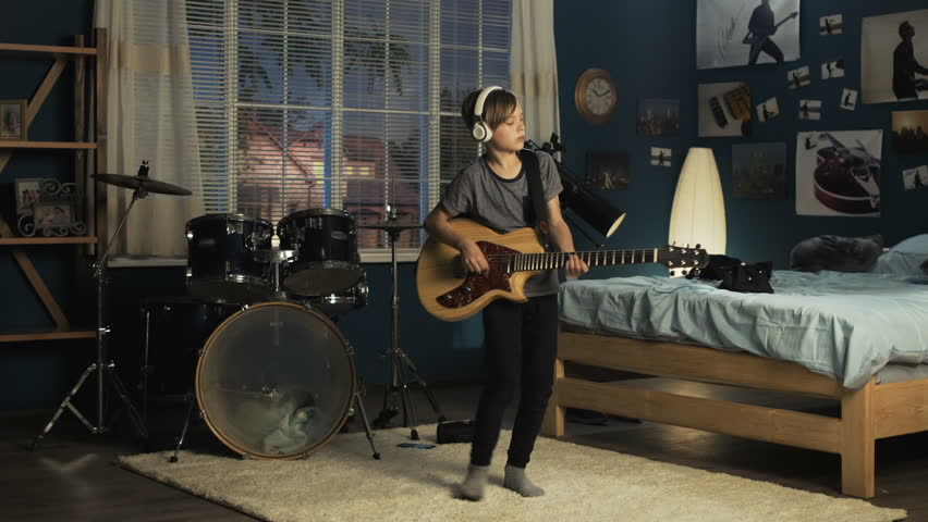 Boy in headphones moving on carpet in bedroom and playing guitar in dreams of being rock star in future