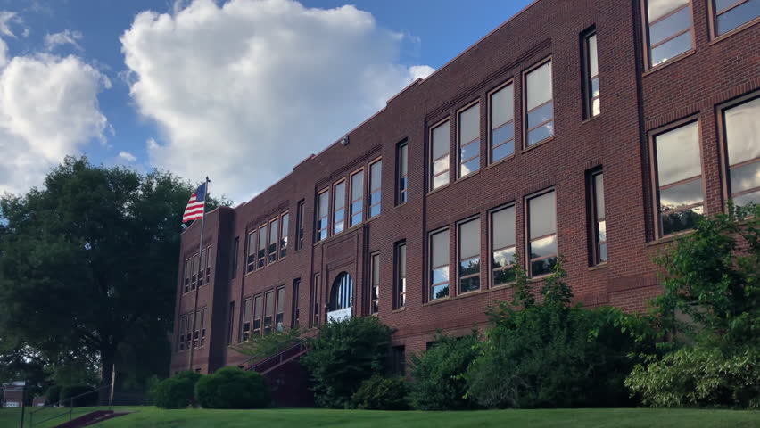 A daytime summer establishing shot of a typical red brick school building in a small town. American flag waving on flagpole in front.