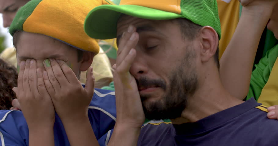 Father and son crying in disappointment after defeat at sports match