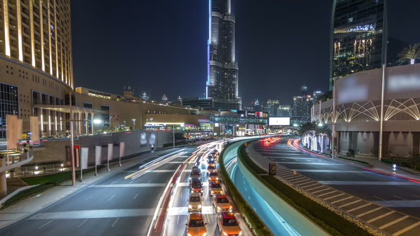 Car traffic on road near mall at night in downtown timelapse hyperlapse. Skyscrapers with night illumination. Top view from bridge. Dubai, UAE