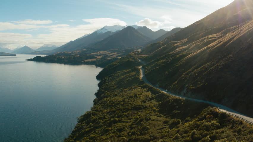 Road trip in New Zealand countryside beside blue lake. White van/campervan driving down long winding road.