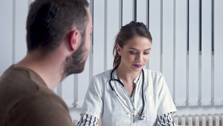 Female doctor using tablet for diagnostics. Young health professional uses tablet to explain health issues to a male patient, at her office. | Shutterstock HD Video #1011923711