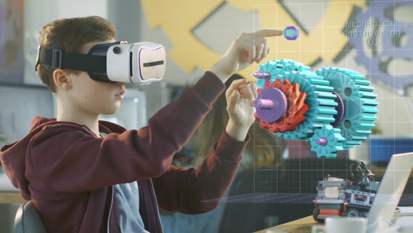 In a Computer Science Class Boy Wearing Virtual Reality Headset Works in Interactive 3D Environment. Mechanical Modeling Project of Connecting Gears with Augmented Reality Software. 4K UHD.