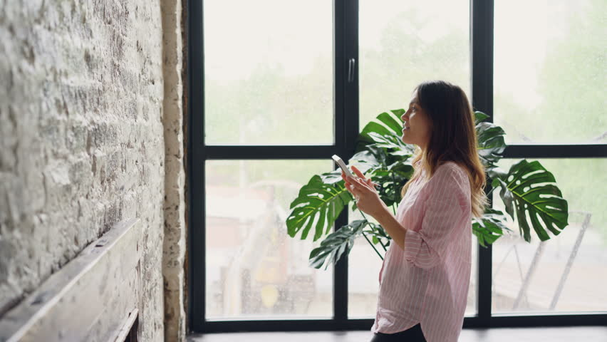 Pretty brunette house owner is decorating her loft style room hanging picture on brick wall choosing place. Interior design, housework, decorating apartment and people concept. #1011936701
