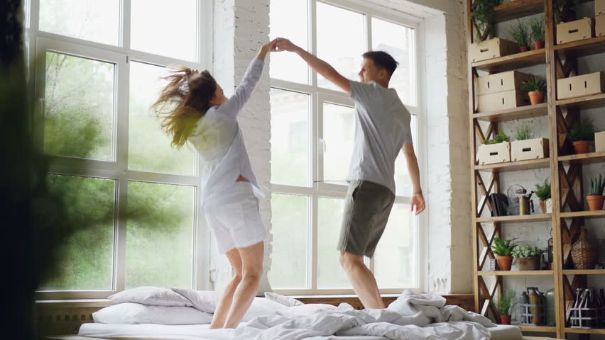Slow motion of cute couple dancing on bed, jumping and laughing together having fun on weekend morning in nice light apartment. Happy people and entertainment concept.