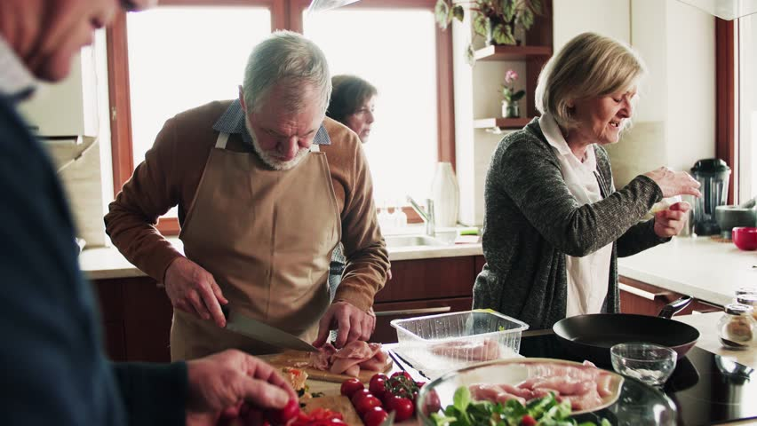 Senior couple cooking dinner together with friends at home.   Shutterstock HD Video #1011945497