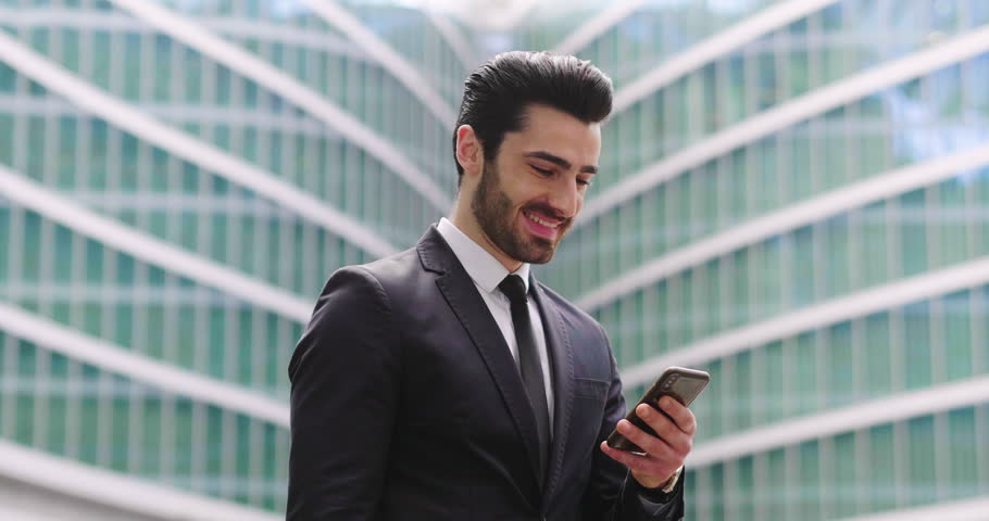 An business man in a suit and tie is happy and smiling while sending messages, working emails or calling using the phone. Concept of: technnology, network, success. #1011947519