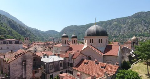 Flight of the quadrocopter over ancient church in Old Town of Kotor. Aerial view of Old Town Kotor, its mountains and Adriatic sea