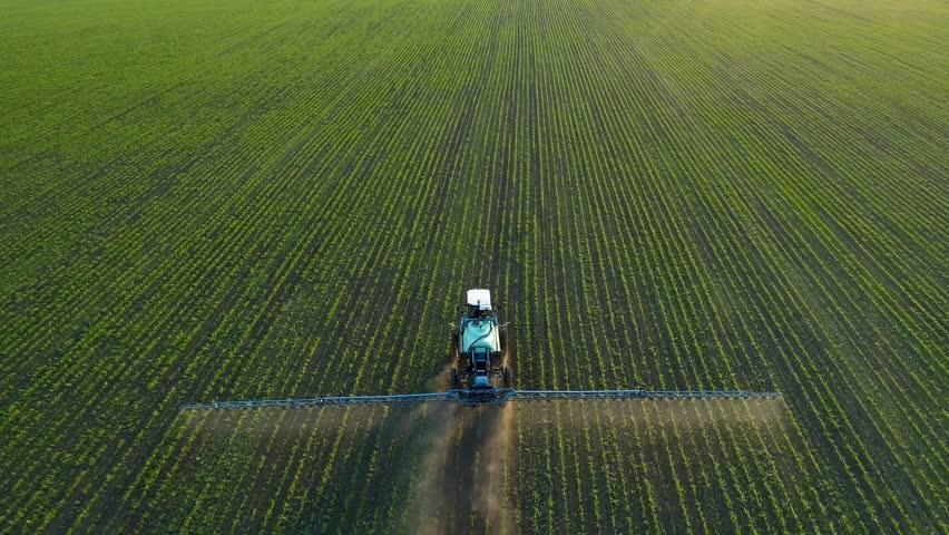 4K aerial drone footage. Following tractor sprayer on soybean fields #1011952670