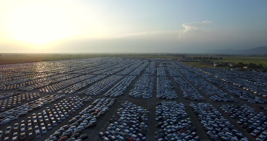 Aerial video of stock car parking. Flying over big industrial zone with big parking lot of brand new cars. Many cars waiting for sale and transportation. Automobile industry.