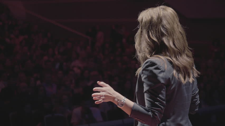 The female financial coach emotional gesturing talks from the stage with spectators at forum. Too many anonymous persons workers and students seat in large auditorium and watch workshop background