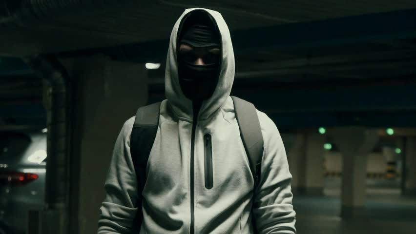 Man bandit in balaclava and hood looking at the camera