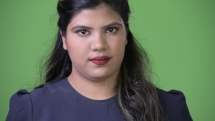 Young overweight beautiful Indian businesswoman against green background | Shutterstock HD Video #1011961889