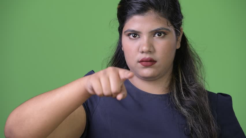 Young overweight beautiful Indian businesswoman against green background | Shutterstock HD Video #1011962645