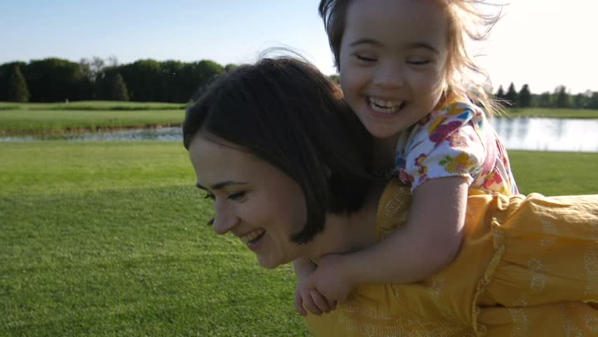 Slow motion of young mother and special needs daughter running on green grass meadow. Mother giving piggyback ride to toddler girl with down syndrome. Delighted girl smiling and laughing in delight