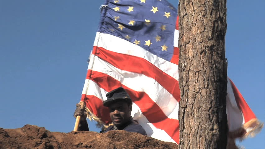 "VIRGINIA - JUNE 2017 - Reenactment - Civil War 54th Massachusetts Black Soldier stands tall on earthworks with U.S. Flag after battle. ""Glory"" movie.  African-American military history. Heroic"