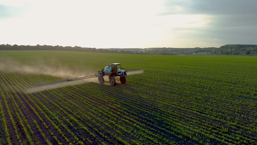 4K aerial drone footage. Tractor sprayer on soybean fields at sunset