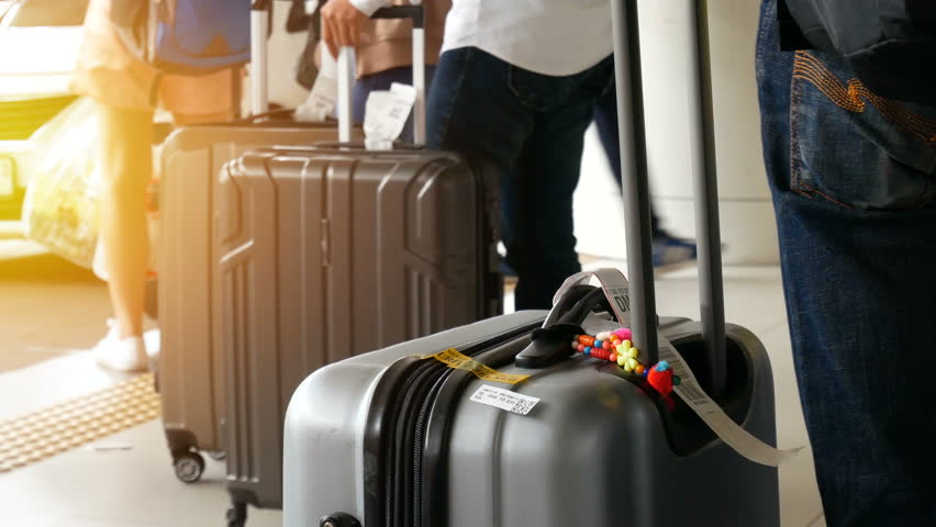 passenger with big roller luggage standing on the line waiting for taxi queue at taxi parking lot at airport arrival terminal Royalty-Free Stock Footage #1011983027