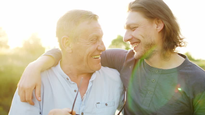 Father and son have a good time on the river bank. Evening sunset. The men talk and laugh. Father takes off his glasses and rubs his eyes. Fathers day