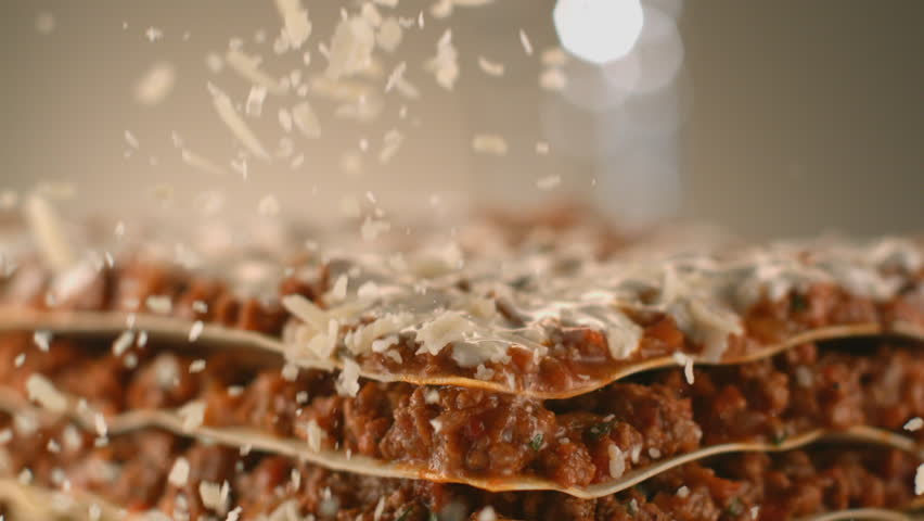 Appetizing meat lasagna is sprinkled with pieces of grated cheese. Parmesan.Very beautiful studio shot. Slow motion. Camera Phantom Flex 4K. #1011990026