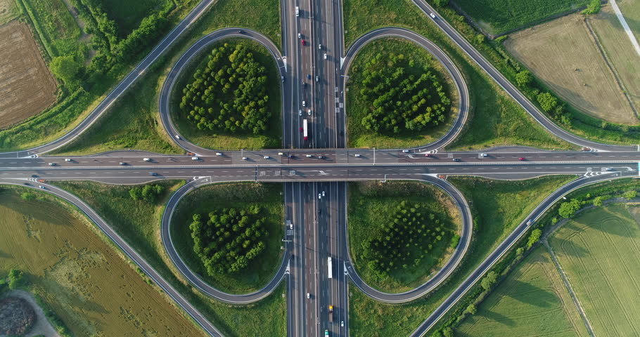 Cloverleaf interchange seen from above. Aerial view of highway road junction in the countryside with trees and cultivated fields. Bird's eye view.   Shutterstock HD Video #1011991637