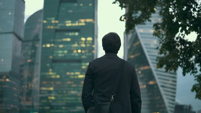 Rear view of a young unrecognizable businessman walking slowly and looking at skyscrapers in a summer evening. Moscow city background. Tracking medium shot