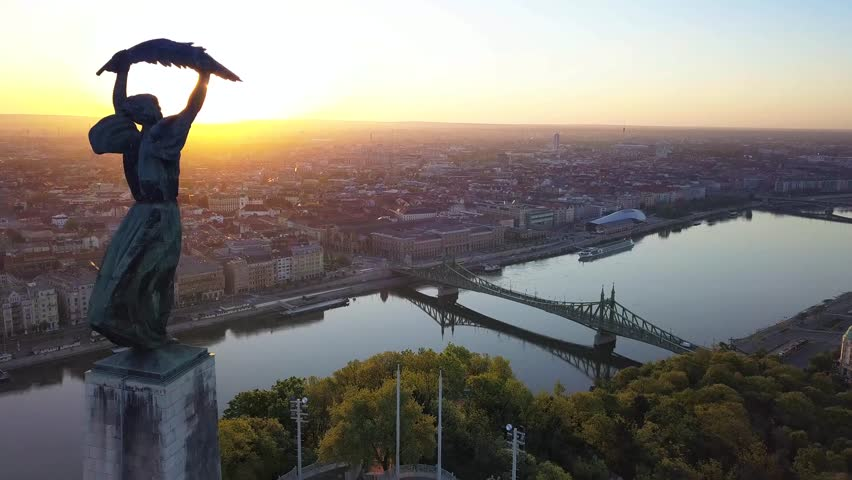 Budapest, Hungary - 4K aerial view of Statue of Liberty on Gellert Hill, Liberty Bridge and skyline of Budapest at sunrise | Shutterstock HD Video #1012012871