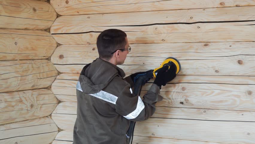 People polish the wall of a wooden house from logs #1012035767