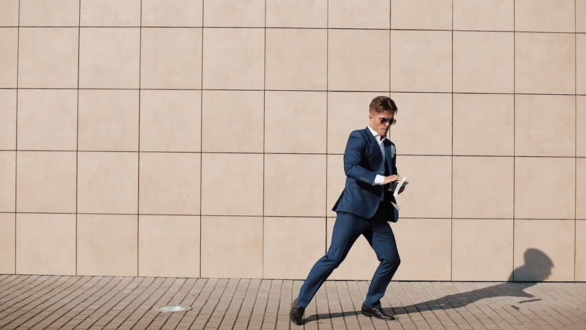 Young happy businessman scatter the dollars and dancing in the street. It is located near the office center, slow motion. Successful business