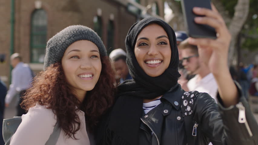portrait of two young woman friends close up of multi ethnic girlfriends posing making faces taking selfie photo using smartphone enjoying hanging out #1012052483