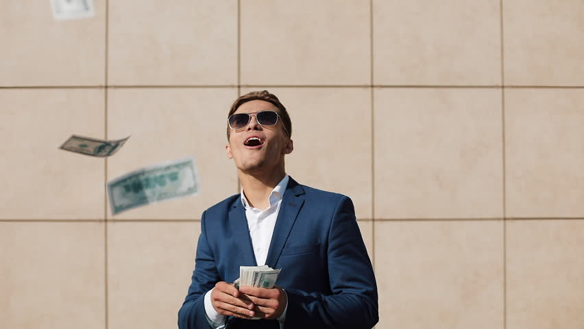 Young happy businessman dancing and throwing money. Slow motion. Successful business or winning the lottery