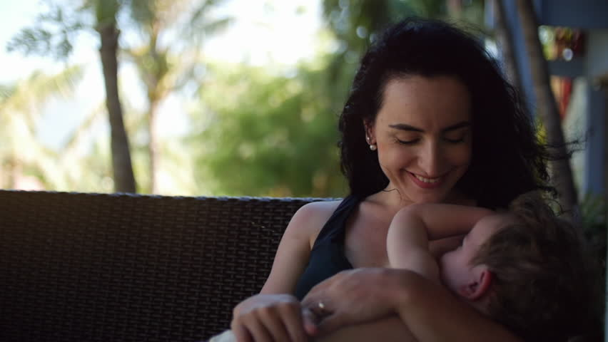 Mom with a child outdoors, breastfeeding him, giving breast milk to a child lulling toddler.
