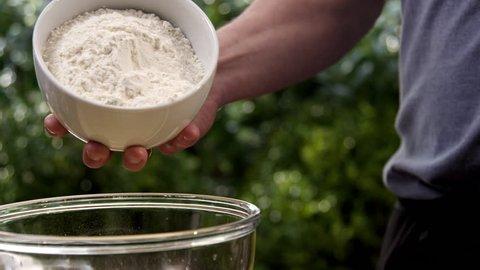 Chef pouring flour into bowl, close up