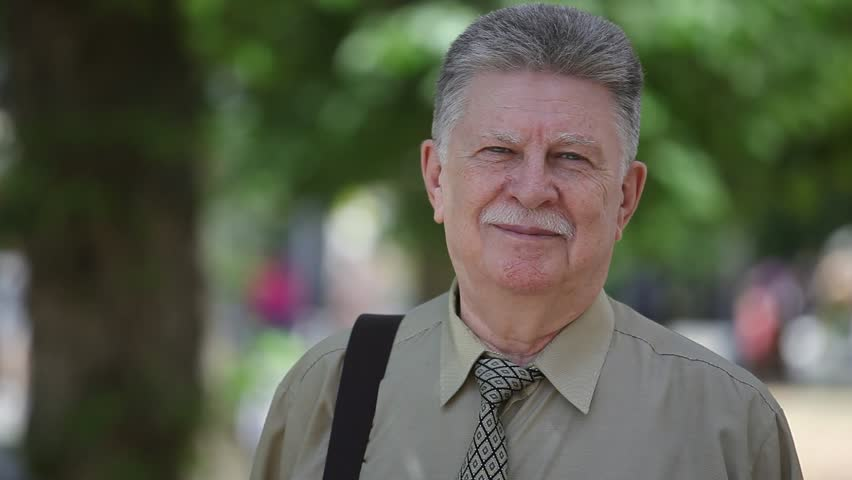 Portrait of an optimistic aged man with brave mustashe dressed in a khaki shirt and a necktie smiling happily in a green alley on a sunny day in summer | Shutterstock HD Video #1012063628