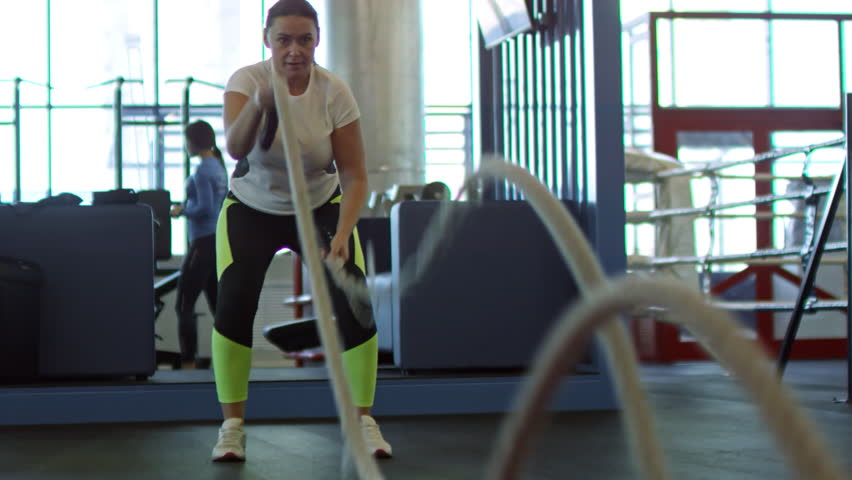 Medium shot of determined middle-aged woman battling ropes in gym during cross-training workout