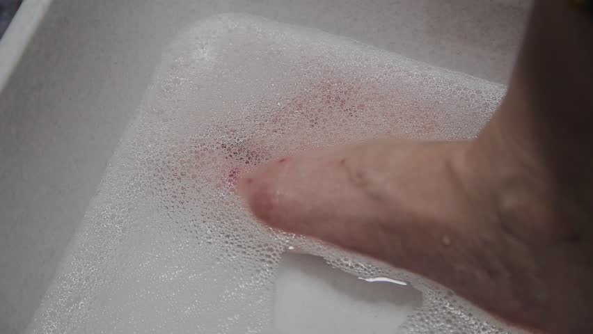 Woman washes her feet in soapy water. | Shutterstock HD Video #1012083266