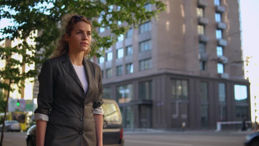Adult beautiful woman walking on the street in early morning. caucasian businesswoman wearing elegant jacket going to work   Shutterstock HD Video #1012090208